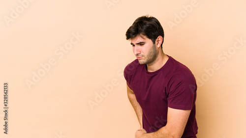 Fototapeta Young man isolated on beige background having a liver pain, stomach ache. obraz