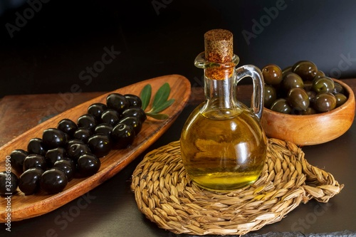 Photo jarra de cristal llena de aceite de oliva, sobre bandeja rústica con aceitunas variadas, fondo negro