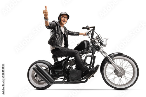 Fotografie, Obraz Cool mature biker in leather clothes riding a chopper and showing thumb up