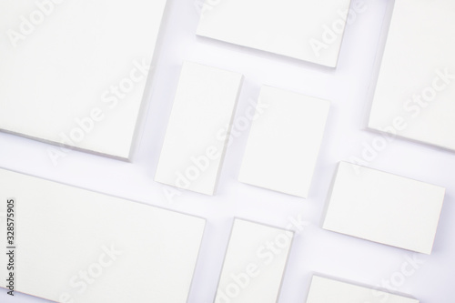 Obraz White cardboard boxes on a white background, concept of shopping and delivery. Many boxes of different sizes, packing goods. Recyclable packaging zero waste. Online shopping, buying with gadgets. - fototapety do salonu