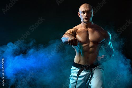 Photo Karate or taekwondo fighter on black background with smoke