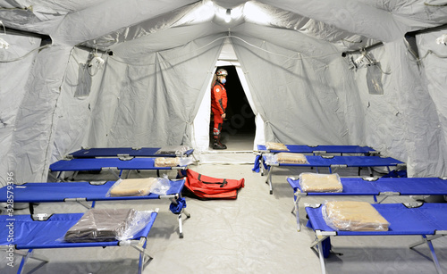 Fototapeta Empty hospital field tent for the first AID, a mobile medical unit of red cross for patient with Corona Virus. Camp room for people infected with an epidemic. obraz