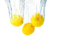 Lemons Splash Into Water And Sinking On White Background.