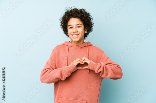 Obraz African american little boy isolated smiling and showing a heart shape with hands. - fototapety do salonu