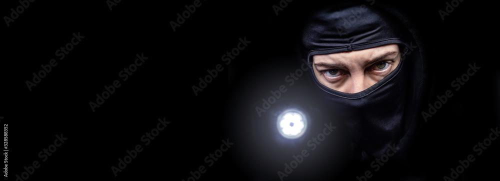 Fototapeta Einbrecher mit Taschenlampe