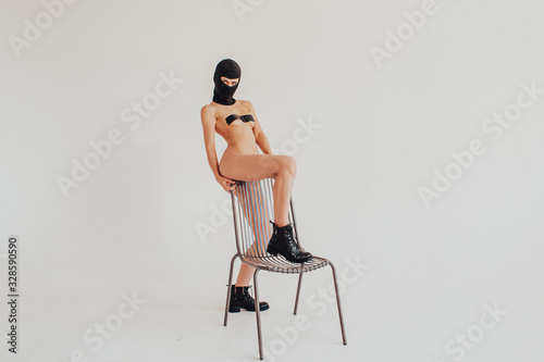 Obraz young beautiful girl in a black mask and black boots, nude on a white background, near a metal chair - fototapety do salonu