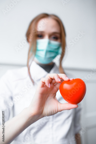 Close up photo Two red-hair cardiologist holding a red toy heart Canvas Print