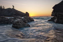 Sun Breaking The Horizon Over A Rocky Cove On An Isolated Beach In Bermuda - Jobsons Cove. Sunrise With Water Swirling In Foreground