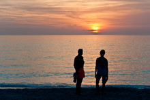 Back View, Far Distance Of Two Woman Watching A Sunset On A Sandy, Tropical Beach On The Gulf Of Mexico