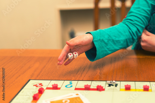 Obraz A girl playing a board game and rolls dice. Hand throws the dice on the background of colorful blurred fantasy Board games, gaming moments in dynamics. selected focus - fototapety do salonu