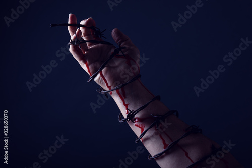 Photo Concept photo of a hand and arm tied with barbed wire artistic conversion