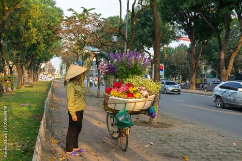 Fototapeta Flower basket on bike of street vendor on Hanoi street. Yellow leaf trees. Autumn or winter season obraz na płótnie