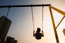 Child Swinging On Swing In Sun...