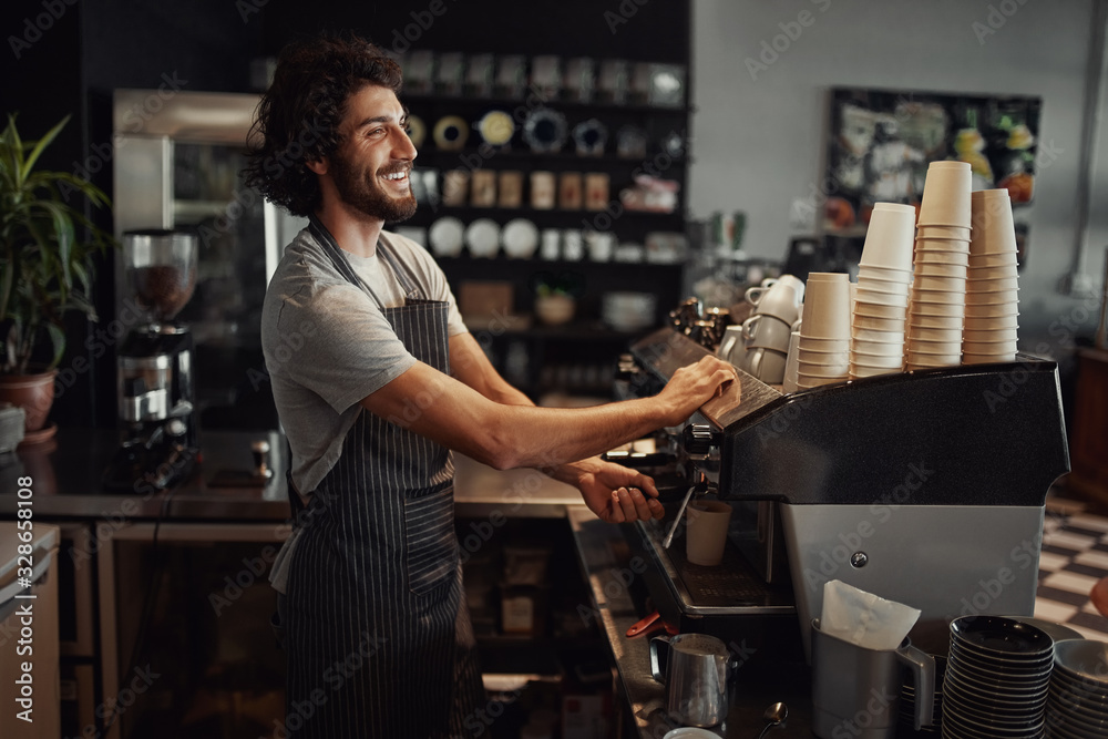 Fototapeta Young cheerful barista wearing black apron while preparing coffee at an automatic machine in a modern coffee shop