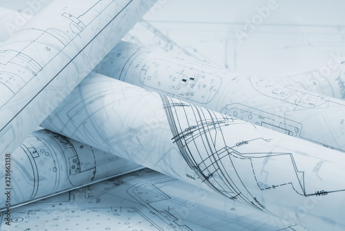 Fototapeta Rolled architectural plans lying on drawing board obraz