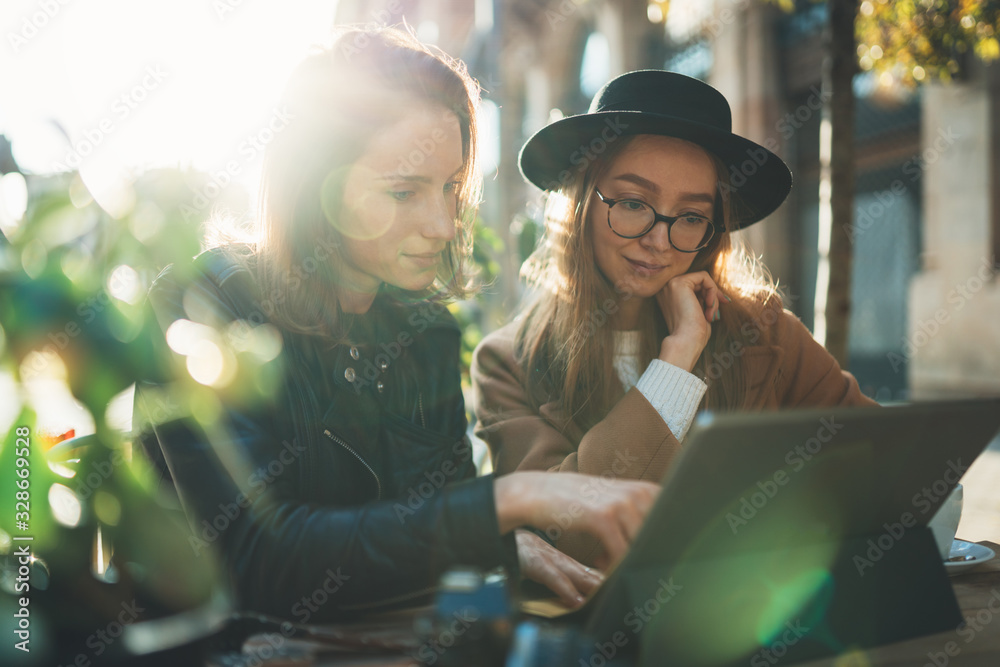 Fototapeta Freelancer communicate on project. Girls using digital tablet. hipster travels in sun city. Business  friendship concept. Internet laptop technology working process project