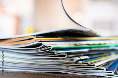 Fotografía Closeup background of a pile of old magazines with bending pages