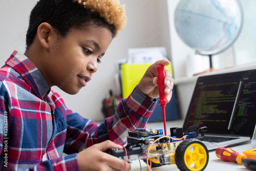 Fototapeta Male Elementary School Pupil Building Robot Car In Science Lesson