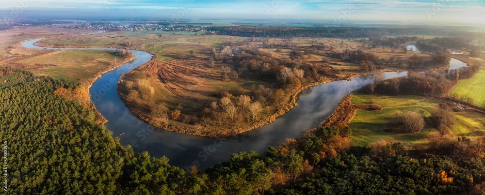 Fototapeta Wijąca się rzeka Warta wśród łąk i lasów Wielkopolski, widok z lotu ptaka