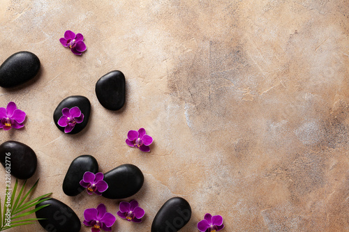 Fototapeta Spa composition with flowers, green leaves and massage stone on brown background top view. Beauty treatment and relaxation concept. Flat lay. . obraz