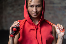 Closeup Portrait Pretty Smiling Sporty Young Woman In Red Hoody Sportswear Hold Skipping Jumping Rope Around Neck Happy Look At Camera Brick Wall Background Weightloss Cardio Healthy,lifestyle Concept