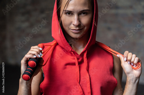 Closeup portrait pretty smiling sporty young woman in red hoody sportswear hold Fototapeta