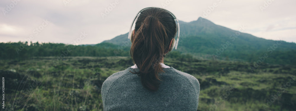 Fototapeta Woman in headphones listening music in nature and at the mountain