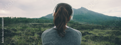 Woman in headphones listening music in nature and at the mountain
