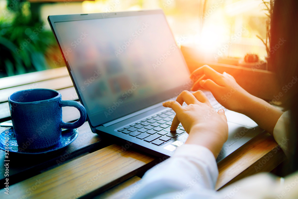 Fototapeta woman hand working on computer laptop with coffee cup beside