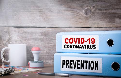 Obraz COVID-19, CORONAVIRUS and PREVENTION. Two binders on desk - fototapety do salonu