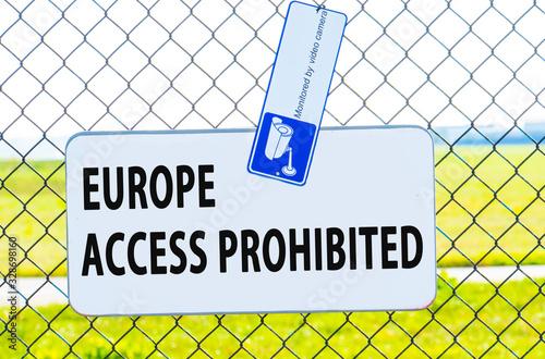 Fényképezés Rectangulardanger sign at a metal border chain-link fence in front of a blue sky