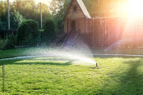 Landscape automatic garden watering system with different sprinklers installed under turf. Landscape design with lawn hills and fruit garden irrigated with smart autonomous sprayers at sunset time
