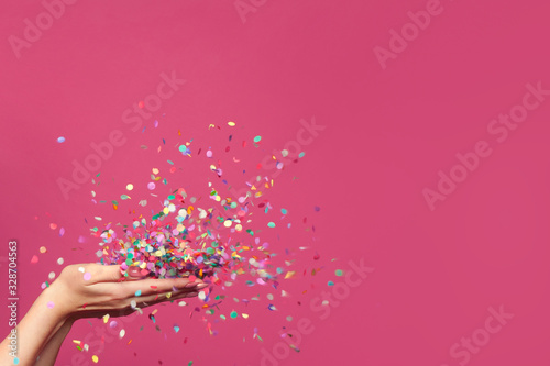 Leinwand Poster Falling confetti on bright pink background
