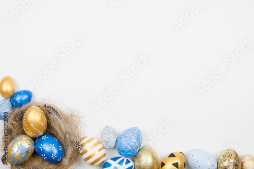 Fototapeta Easter golden decorated eggs in nest isolated on white background for web banner. Minimal easter concept. Happy Easter card with copy space for text. Top view, flatlay. obraz