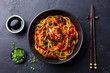 Stir fry noodles with vegetables and beef in black bowl. Slate background. Top view.