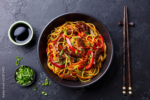 Fototapeta Stir fry noodles with vegetables and beef in black bowl. Slate background. Top view. obraz
