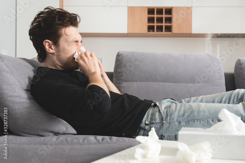 Sick man lying on sofa and blowing nose Canvas Print