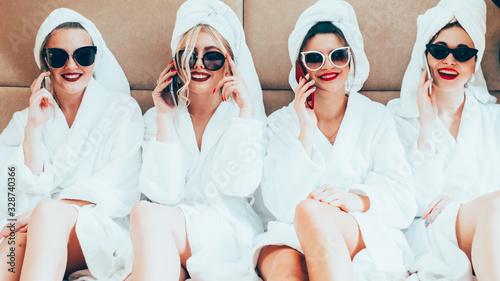 Fototapeta Hen party. Spa therapy leisure. Happy posh women in bathrobes sunglasses talking on phones. obraz