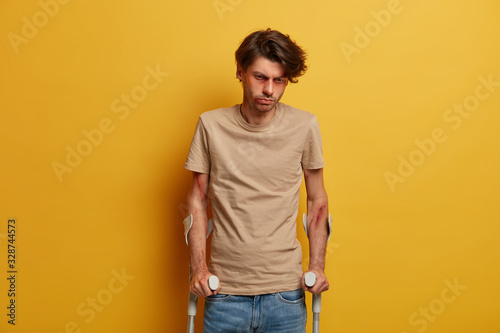 Disabled handicapped bruised man looks sadly down, cannot walk himself for long Canvas Print