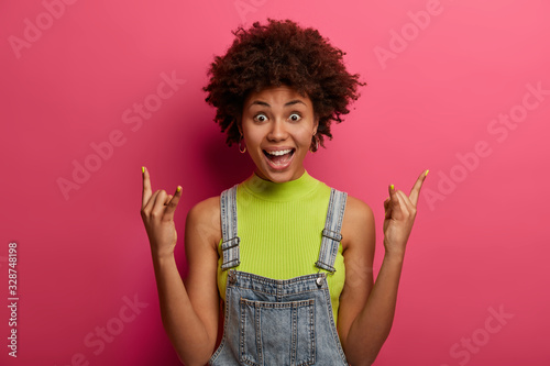 Excited cheerful woman born to be rock star, shows horn hand gesture, enjoys pun Canvas Print