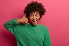 Pretty Delighted Woman Makes Phone Sign, Tells Call Me Back, Smiles Happily, Communicates With Gestures, Dressed In Green Sweater, Poses Over Pink Background. Dont Forget To Call, Being In Touch