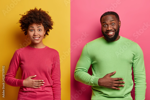 Pleased ethnic young woman and man keep hands on stomach, feel satiety after eat Fototapet