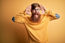 Handsome Irish Redhead Man With Beard Wearing Glasses Over Yellow Isolated Background Smiling Cheerful Playing Peek A Boo With Hands Showing Face. Surprised And Exited