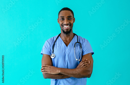 Portrait of a friendly male doctor or nurse wearing blue scrubs uniform and stethoscope  with arms crossed  isolated on blue studio background