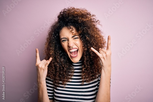 Young beautiful woman with curly hair and piercing wearing casual striped t-shirt shouting with crazy expression doing rock symbol with hands up. Music star. Heavy concept.