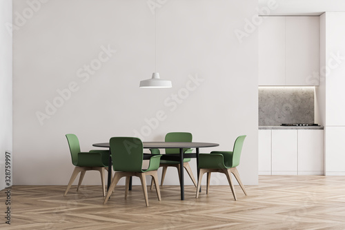 White kitchen with dining table and green chairs