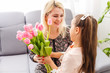 Happy mother's day. Child daughter congratulates moms and gives her flowers tulips
