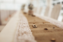 Detail Of Decorated Dining Table With Burlap Tablecloth And White Decorative Lace. On Tablecloth Are Placed Wooden Ornaments In Shape Of Small Hearts. Shallow Depth Of Field. Background Out Of Focus.