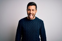 Young Handsome Man With Beard Wearing Casual Sweater Standing Over White Background Sticking Tongue Out Happy With Funny Expression. Emotion Concept.