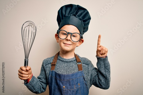 Young little caucasian cook kid wearing chef uniform and hat using manual whisk surprised with an idea or question pointing finger with happy face, number one